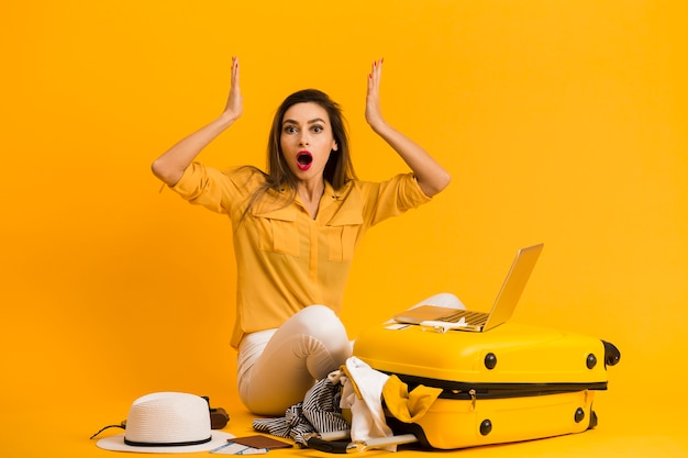 Front view of frustrated woman with laptop on top of luggage