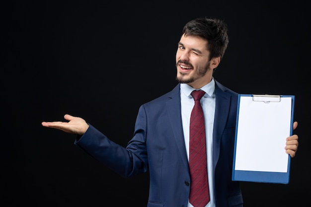 Front view of funny adult in suit holding free space for writing and pointing something on the right side on isolated dark wall