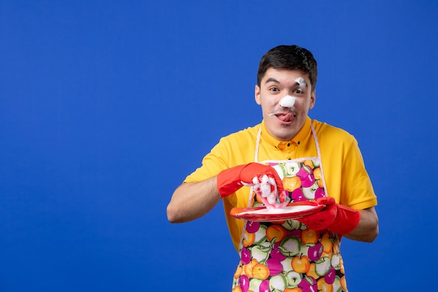 Front view funny cheerful housekeeper with foam on his face washing plate on blue space