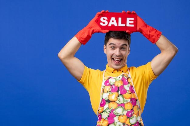 Vista frontale divertente allegra governante in maglietta gialla che alza il cartello di vendita sopra la sua testa su uno spazio blu