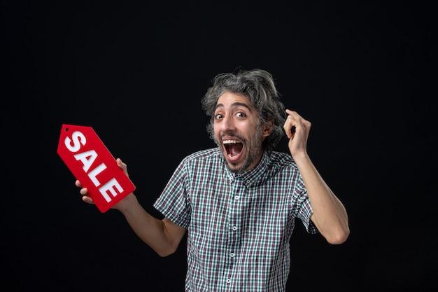 暗い壁に赤い販売サインを保持している正面面白い陽気な男
