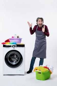 Вид спереди забавный веселый человек, стоящий возле корзины для белья стиральной машины на белом фоне