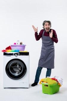Vista frontale divertente uomo allegro in piedi vicino al cesto della biancheria della lavatrice su sfondo bianco