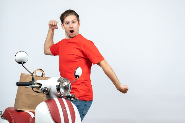 Front view of funny crazy emotional delivery man in red uniform standing near scooter on white background