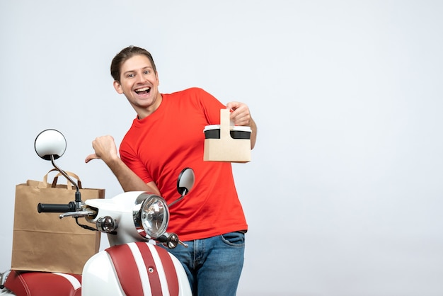 Front view of funny emotional delivery man in red uniform standing near scooter pointing order on white background