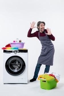 흰색 배경에 세탁기 세탁 바구니 근처에 서 있는 전면 보기 재미있는 가정부 남자
