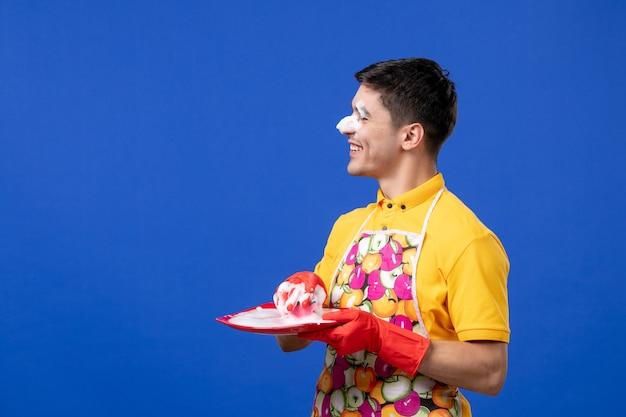 Governante divertente vista frontale con schiuma sul naso che prende schiuma dal piatto su spazio blu