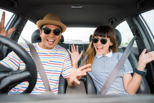 Front view of funny moment couple asian man and woman sitting in car. enjoying travel concept.