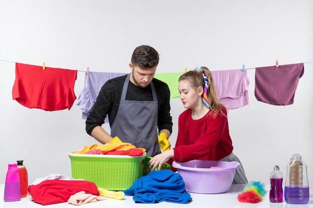Giovane coppia divertente di vista frontale che ordina i vestiti sulla parete bianca