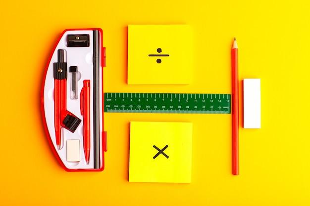 노란색 표면에 스티커와 연필로 전면보기 기하학적 인물
