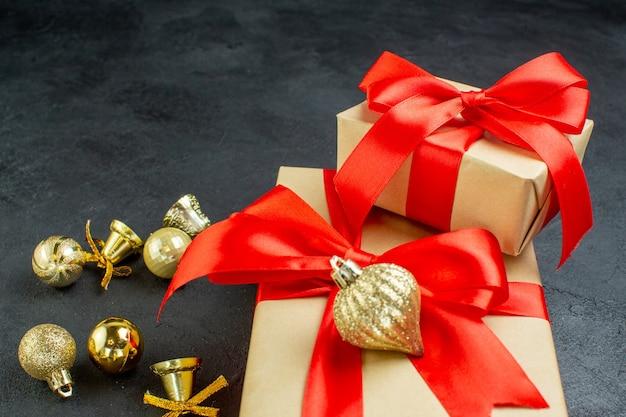 Vista frontale della confezione regalo con nastro rosso e accessori di decorazione su sfondo scuro