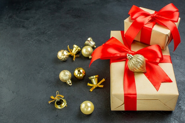 Front view of gift box with red ribbon and decoration accessories on dark background