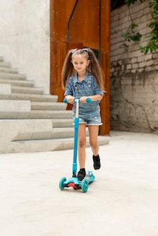 Front view of girl on blue scooter