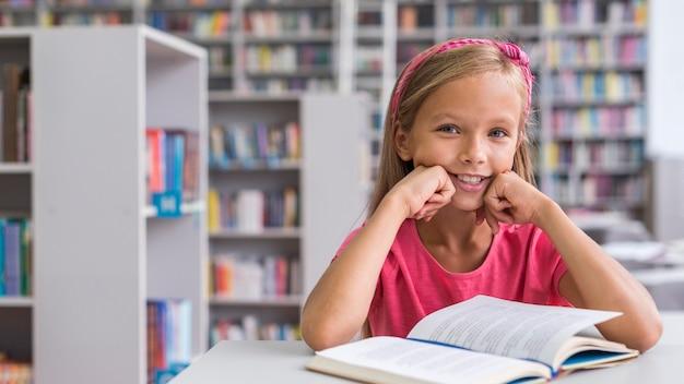 Вид спереди девушка делает домашнее задание в библиотеке