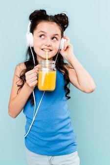 Front view girl drinking juice and listening music