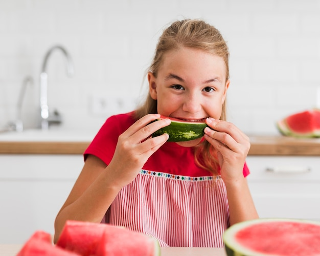 Front view of girl eating watermelon