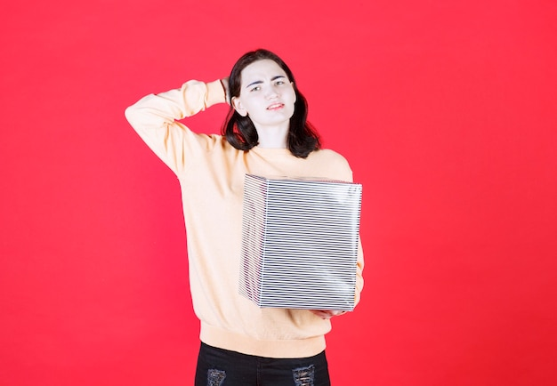 Front view of girl hold gift box and scraping her head isolated on a red wall