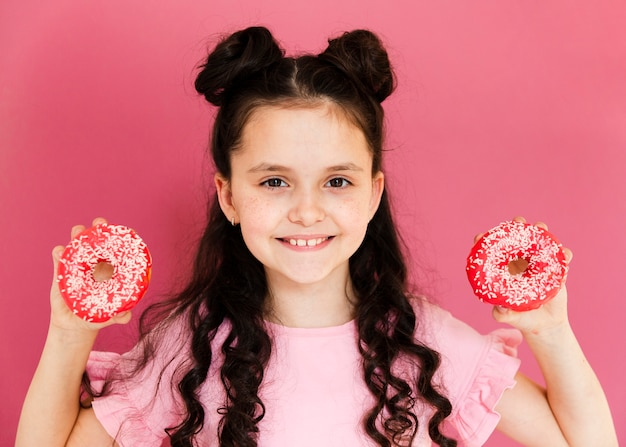 Front view girl holding doughnuts in her hands