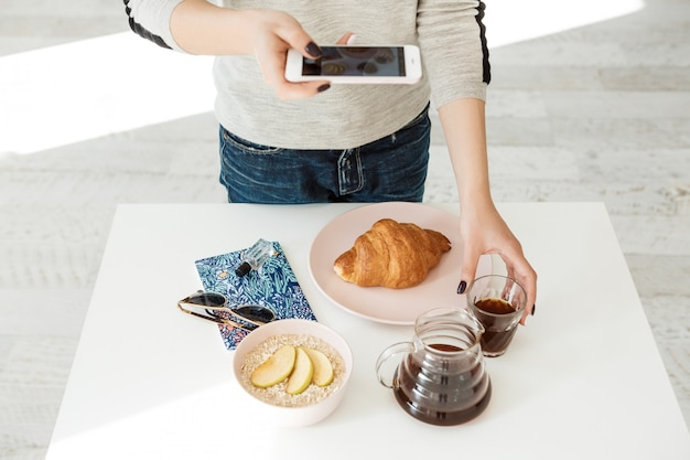 Front view of girl holding phone while shooting tasty breakfast.