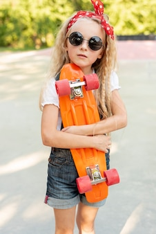 Front view of girl holding skateboard