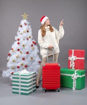 크리스마스 트리와 선물 근처에 서 뭔가 보여주는 그녀를 들고 전면보기 소녀
