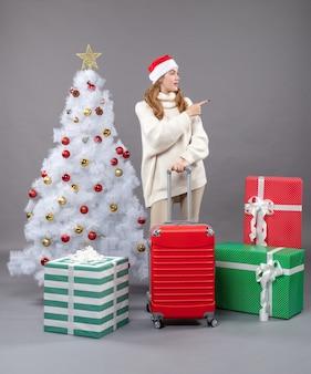 Valigia della holding della ragazza di vista frontale che mostra qualcosa che sta vicino all'albero di natale ed ai regali