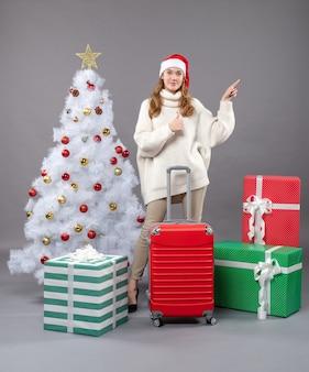 クリスマスツリーとギフトの近くに立っているサンタの帽子をかぶってスーツケースを保持している正面図の女の子