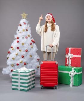 Вид спереди девушка держит чемодан с поднятой рукой, стоя возле елки