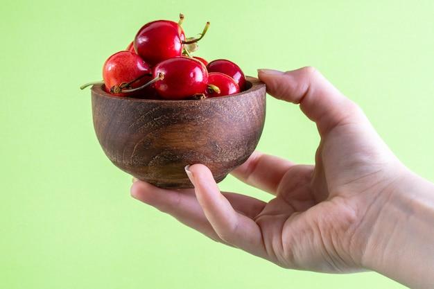 Vista frontale la ragazza tiene in mano le ciliegie in una ciotola di legno su verde chiaro