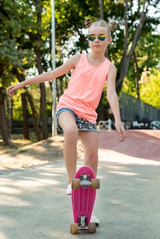 Front view of girl on pink skateboard