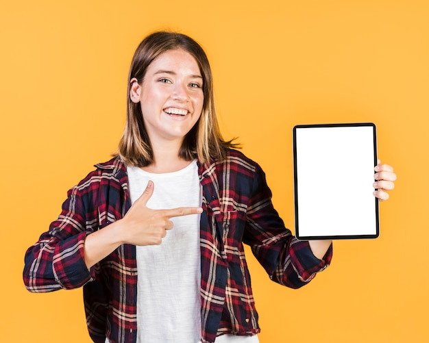 Front view girl pointing at a tablet