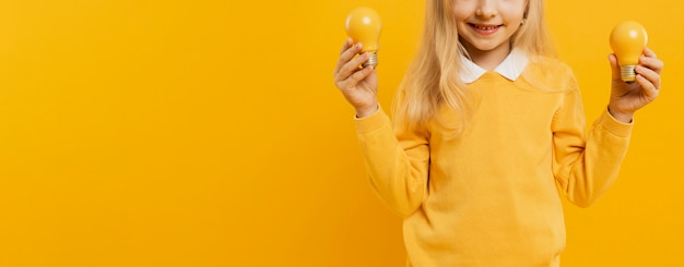 Front view of girl posing while holding yellow light bulbs