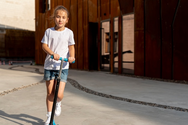 Front view of girl riding blue scooter