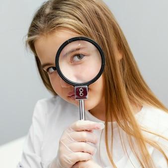 Vista frontale dello scienziato della ragazza che tiene la lente d'ingrandimento