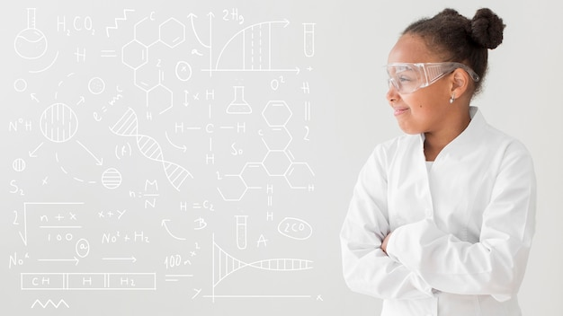 Front view of girl scientist posing with lab coat and safety glasses