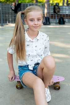 Front view of girl sitting on skateboard