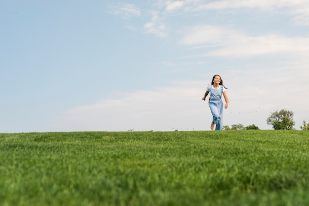 Front view girl walking barefoot on grass