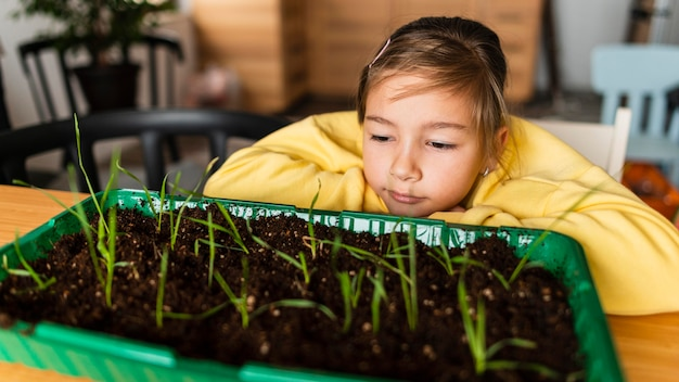 Front view of girl watching sprouts grow at home