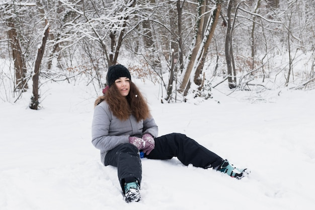 Front view of girl wearing warm clothes sitting on snow