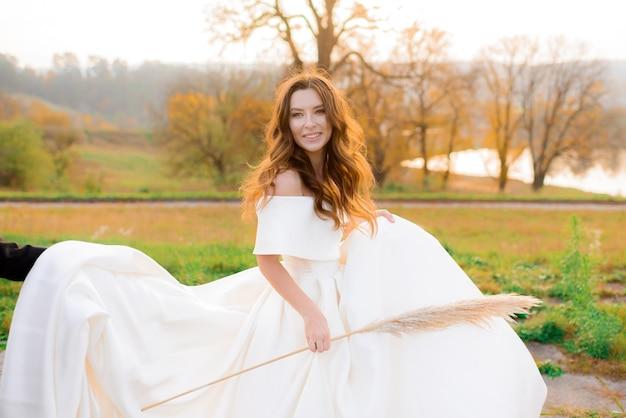 Vista frontale di una ragazza in abito bianco con una spiga di grano in mano che sorride nel parco autunnale
