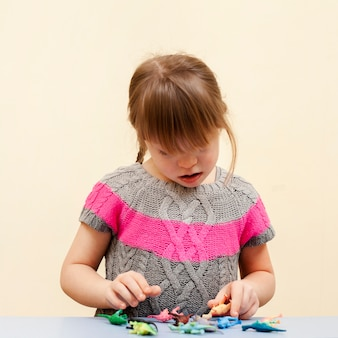 Front view of girl with down syndrome and toys
