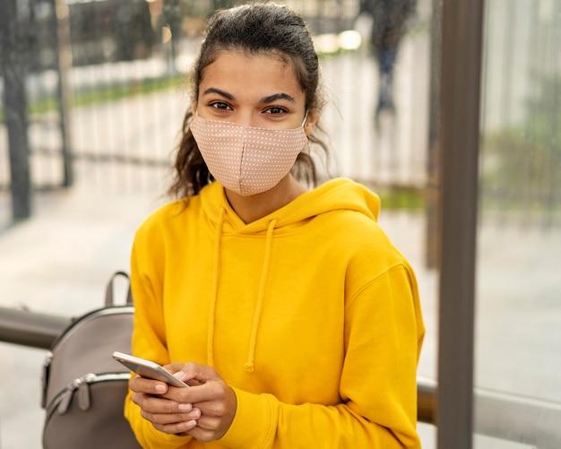 Vista frontale della ragazza con la maschera per il viso sulla strada