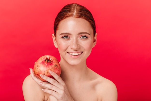 Front view of girl with garnet expressing happiness. studio shot of laughing ginger woman with pomegranate isolated on red background.