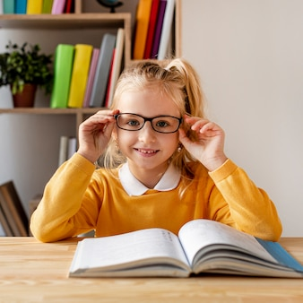 Front view girl with glasses reading