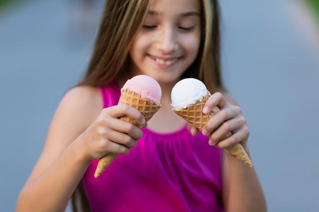 Vista frontale della ragazza con i coni di gelato
