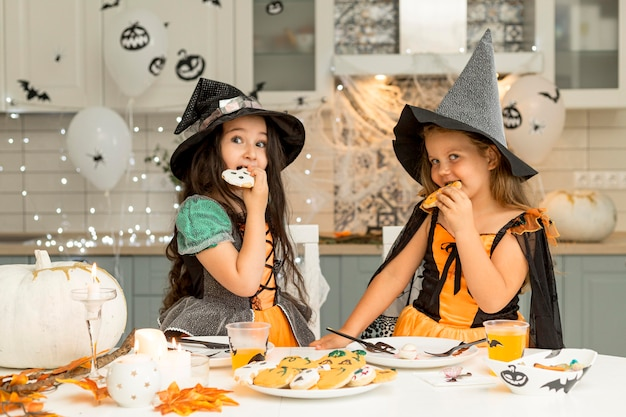 Front view of girls eating halloween cookies