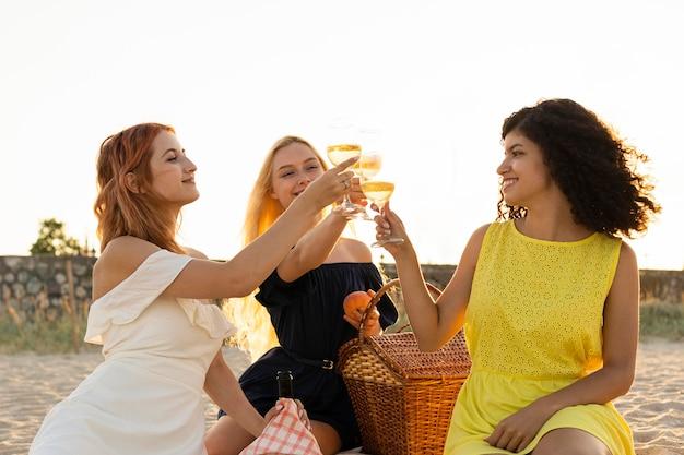 Vista frontale delle ragazze che hanno un picnic in spiaggia