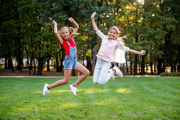 Front view of girls jumping in the park