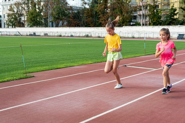 Front view of girls running on track