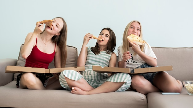 Front view girls sitting on sofa and eating a pizza